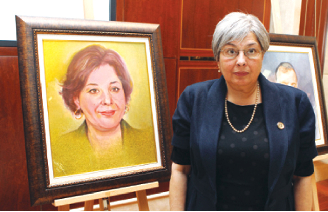 رضوى عاشور بجانب لوحة فنية رسمت لها في مؤسسة العويس الثقافية