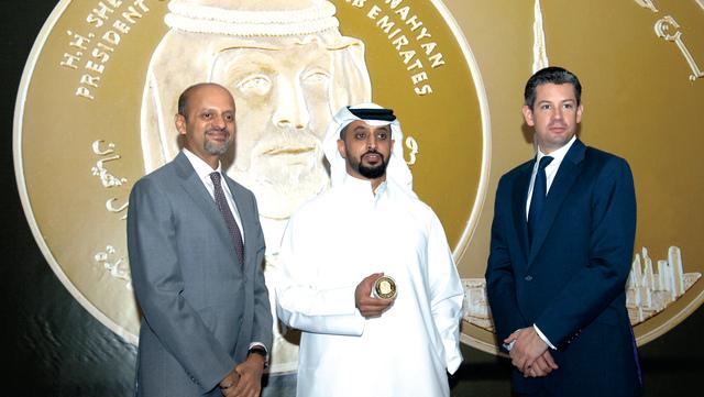 الصورة : أحمد وسلطان بن سليم أمام مسكوكة عالمية صنعت في دبي باسم «عملة البليون» الذهبية