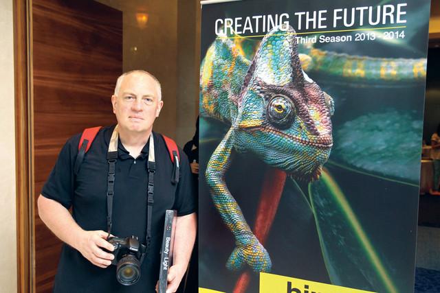 الصورة : الفائز كلاوس بيتر سيزلر بجانب صورته في ملصق الدورة الثالثة