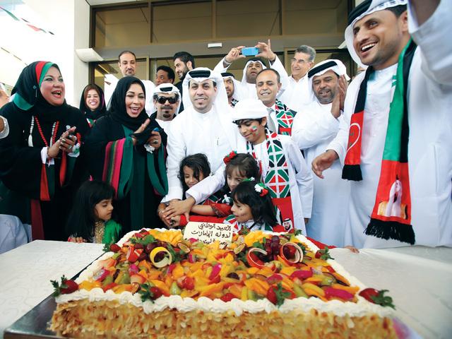 الصورة : ظاعن شاهين وعلي شهدور وفضيلة المعيني وعدد من الزملاء والأطفال أثناء قطع قالب الحلوى
