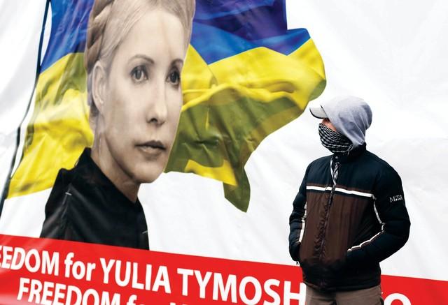 متظاهر يقف أمام ملصق لزعيمة المعارضة يوليا تيموشينكو في كييف رويترز