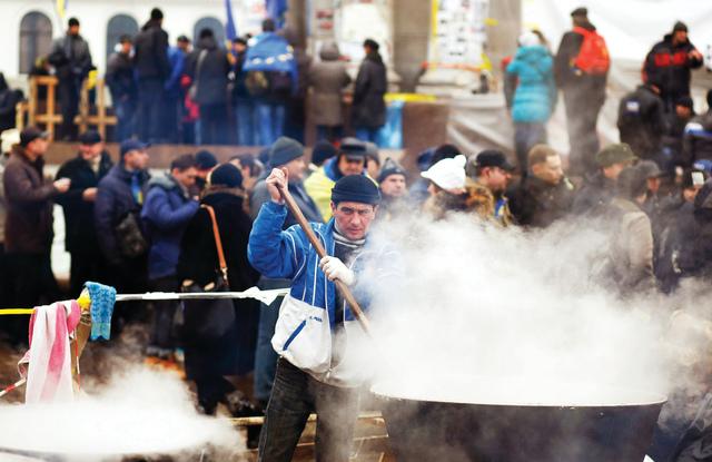 معارض أوكراني يعدّ الطعام لتوزيعه على المحتجين في ساحة الاستقلال  رويترز