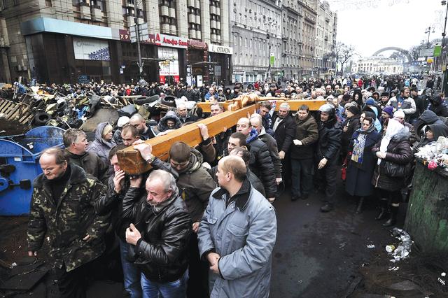متظاهرون أوكرانيون في كييف خلال موكب ديني لضحايا الاحتجاجات الأخيرة أ.ف.ب