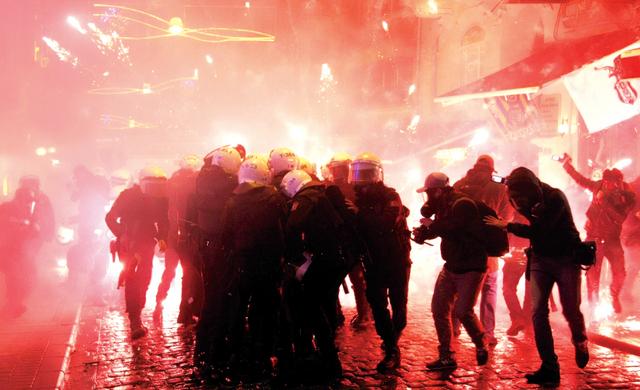 الصورة : الشرطة التركية تحاول الاحتماء من ألعاب نارية أطلقها متظاهرون عليها في إسطنبول أثناء الاحتجاج على قانون يقيد حرية الأنترنيت إي.بي.إيه