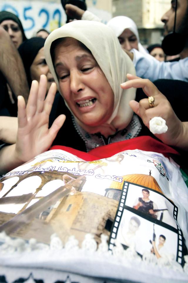 فلسطينية تبكي جثمان ابنها الشهيد منذ 2003 وتم تسليمه في طولكرم الاثنين أ.ف.ب