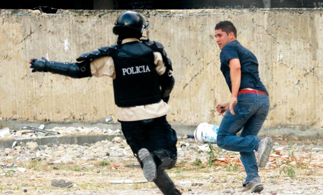 شرطي يلاحق متظاهرا في ساحة التاميرا وسط كاراكاس                        رويترز