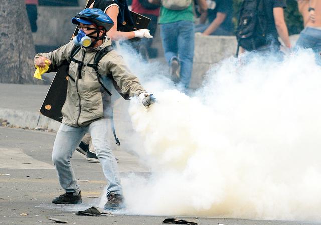 الصورة : .. ومحتج يلقي قنبلة بدائية الصنع على قوات الأمن في العاصمة                           أ.ف.ب