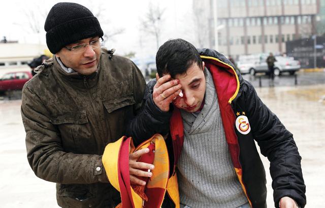 الصورة : متظاهر تركي يساعد صديقاً له أصيب في الاحتجاجات إي.بي.إيه