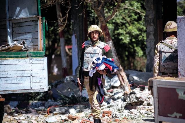 الصورة : جندي يحمل ملابس كانت ملقاة على الأرض في موقع التفجير  أ.ب