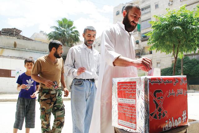 الصورة : معارضون للنظام في حلب يدلون بأصوات في صندوق أحمر في انتخابات تسخر من انتخابات نظام الأسد      أ.ف.ب
