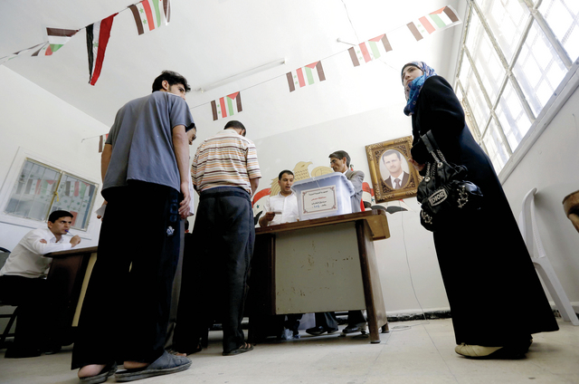 الصورة : ناخبون في بابا عمرو المدمر بحمص يدلون بأصواتهم       أ.ف.ب