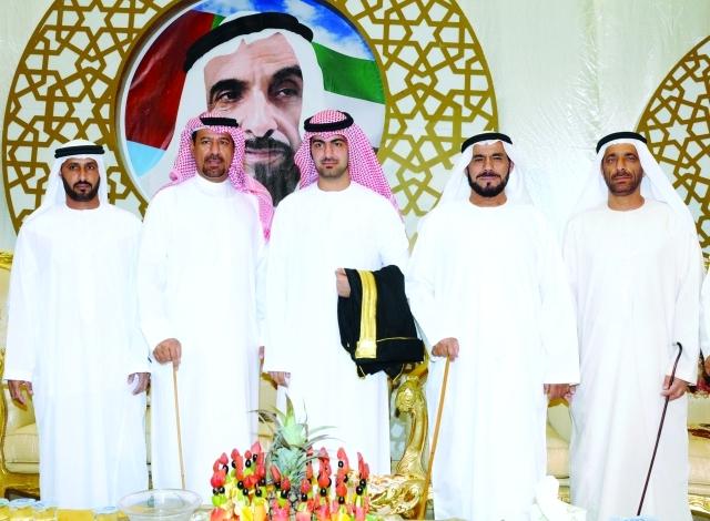 الصورة : العريس يتوسط عبيد محمد الكعبي ووالده علي الكعبي وعدداً من الحضور