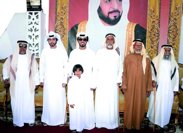 الصورة : العريسان وعدد من المهنئين
