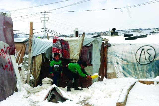 الصورة : ■ طفل سوري يحاول إزاحة الثلوج من أمام خيمته بمعسكر لاجئين في سهل البقاع اللبناني  |  أيه.بي.ايه