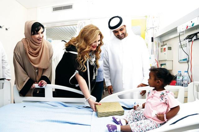 الصورة : جمعة آل مكتوم ومريم عثمان خلال تقديم الهدايا للمرضى    تصوير: عبد الحنان