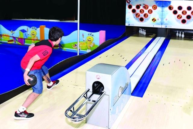 الصورة : طفل يسدد ضربته بتركيز في لعبة البولينغ       من المصدر