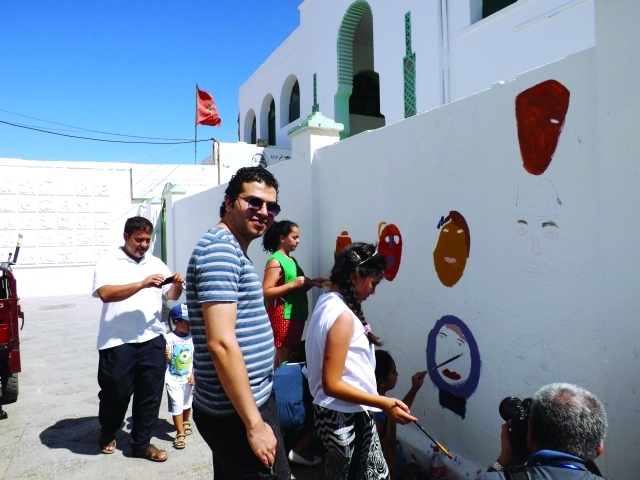 الصورة :  علي ميرزا مع الأطفال خلال رسم جدارية في أصيلة  | البيان
