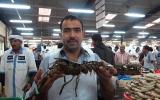 """الصورة: كبار السن في سوق سمك """"ديرة"""" خبرة معجونة بروائح البحر"""