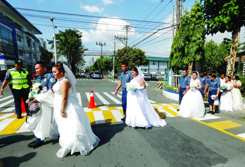 ■ أزواج من الفلبين يمرون وسط حراسة الشرطة     إي بي إيه