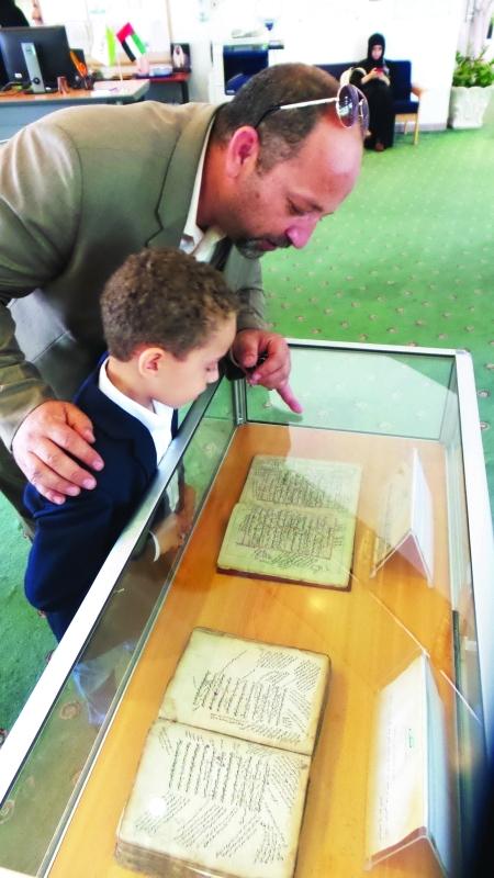 ■ والد يقرأ لطفله من أحد المخطوطات