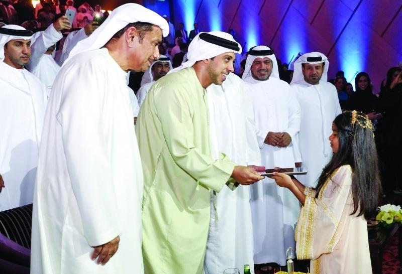 الصورة : ■ منصور بن زايد يتسلم لوح زر انطلاقة البطولة من الطفلة عوشة الفلاسي بحضور هلال الكعبي |  البيان