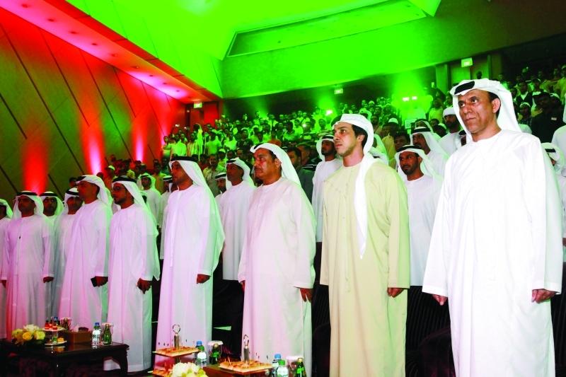الصورة : ■ .. وسموه أثناء عزف النشيد الوطني وإلى جواره هلال الكعبي ومحمد بن ثعلوب وكبار الحضور