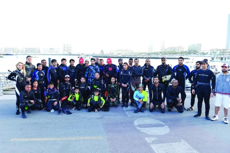 الصورة : ■ حمدان بن محمد متوسطاً فريق الغوص المشارك في مبادرة تنظيف قاع الميناء السياحي |  تصوير: محمد هشام