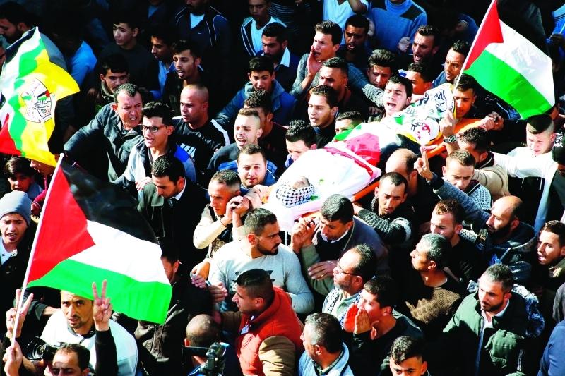 الصورة : ■ فلسطينيون يشيّعون جثمان الشهيد محمد أمين في بلدة بيت أولا شمال غربي الخليل      أ.ف.ب