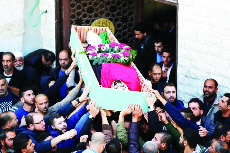 الصورة : ■  فلسطينيون يشيّعون جثمان الشهيد باسل مصطفى في بلدة عناتا شمال شرقي القدس المحتلة      رويترز