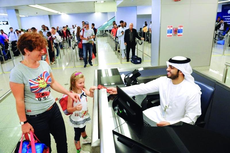 الصورة : ■  موظفو جوازات دبي يرسمون البسمة على وجوه ضيوف الدولة     من المصدر