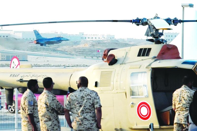 الصورة : Ⅶ جنود بحرينيون يقفون إلى جانب مروحية تابعة لسلاح الجو الملكي خلال معرض البحرين الدولي للطيران في قاعدة الصخير الجوية   أ.ف.ب
