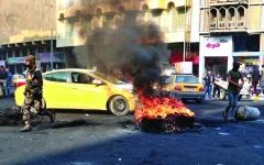 الصورة: الصورة: عراقي يحرق سيارته الإيرانية الصنع  في ساحة التحرير