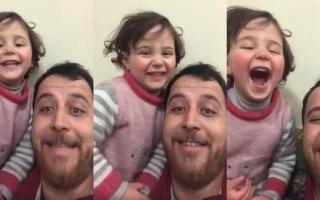 الصورة: الصورة: بالفيديو .. أب سوري يحول ضجيج القنابل إلى ضحكات ليحمي ابنته