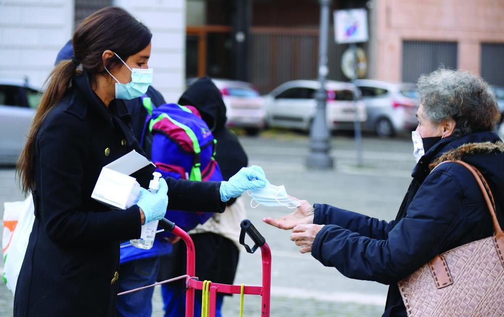 الصورة : متطوعة إيطالية توزّع الأقنعة الواقية بمنطقة تراستيفيري في روما رويترز