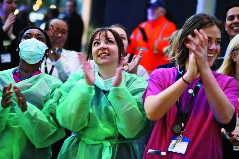 الصورة : موظفات في الصحة البريطانية يتفاعلن مع حملة تضامن شعبية / رويترز