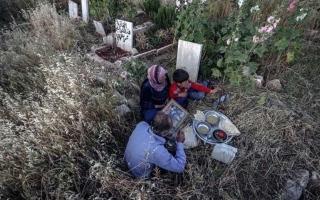 الصورة: الصورة: صورة لعائلة سورية تفطر بين القبور تشعل مواقع التواصل