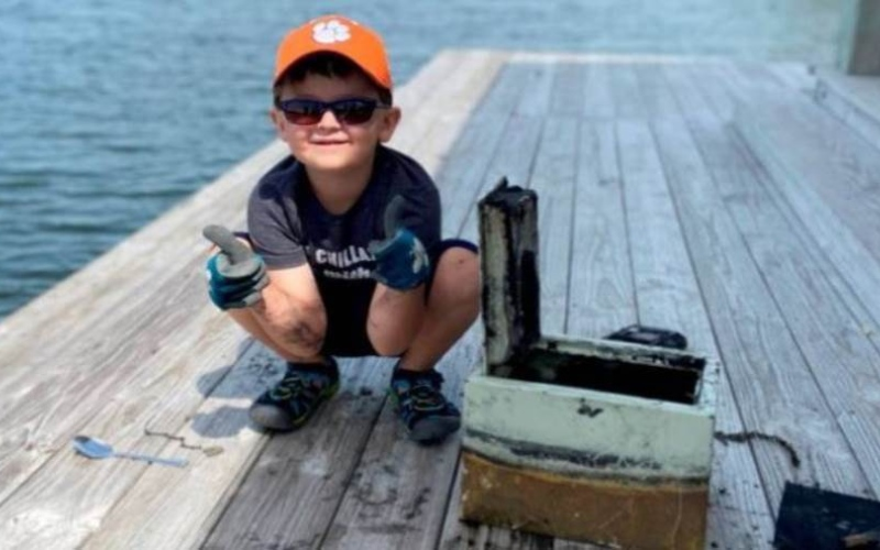 الصورة: الصورة: طفل يصطاد كنزاً ثميناً من قاع بحيرة