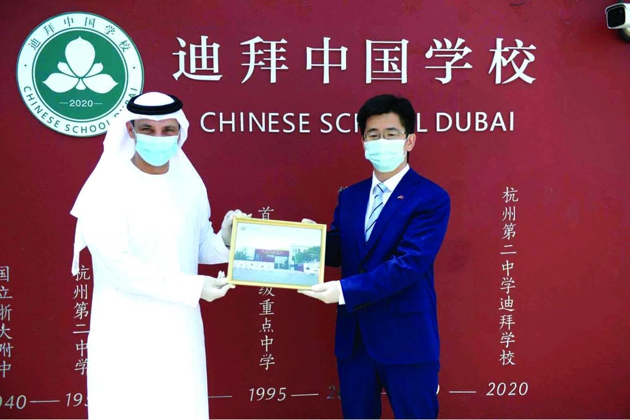 الصورة : عبدالله الكرم والقنصل الصيني خلال تفقدهما مقر المدرسة   وام