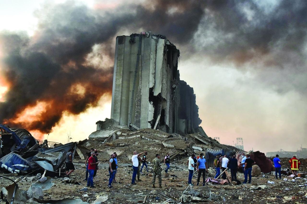 الصورة : سكان وناجون بالقرب من صوامع بيروت التي تعرضت لدمار هائل   أ.ف.ب