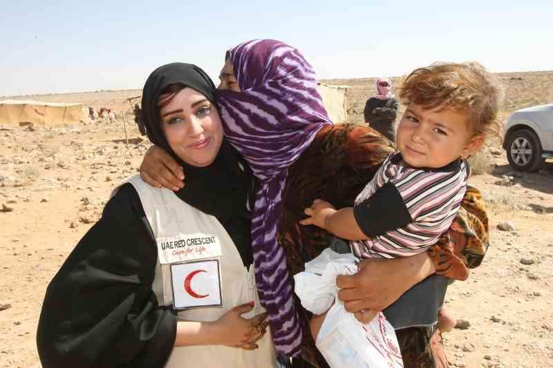 الصورة : لاجئة سورية في الأردن تقبل موفدة الهلال الأحمر الإماراتي | أرشيفية