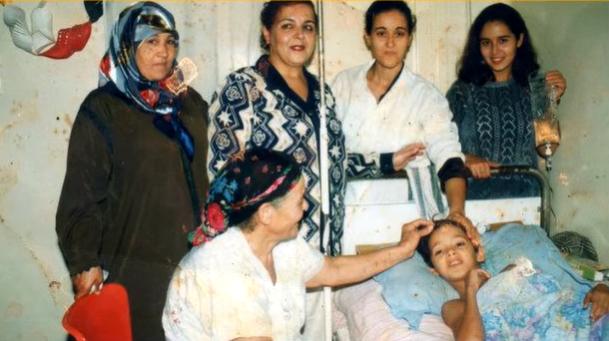 الصورة : إبراهيم في سن 11 وسط أهله بعد عملية البتر