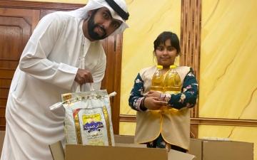 الصورة: الصورة: نورة النيادي.. طفلة مواطنة توزع المير الرمضاني على الأسر المتعففة