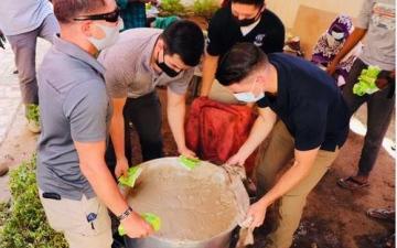 الصورة: الصورة: أمريكيون وسودانيون جنباً إلى جنب في تجهيز وجبة الإفطار