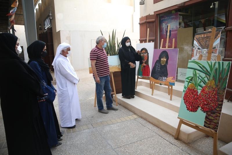 الصورة : عزة الكتبي تتحدث عن لوحات معرضها أمام عدد من الزائرين   تصوير: إبراهيم صادق