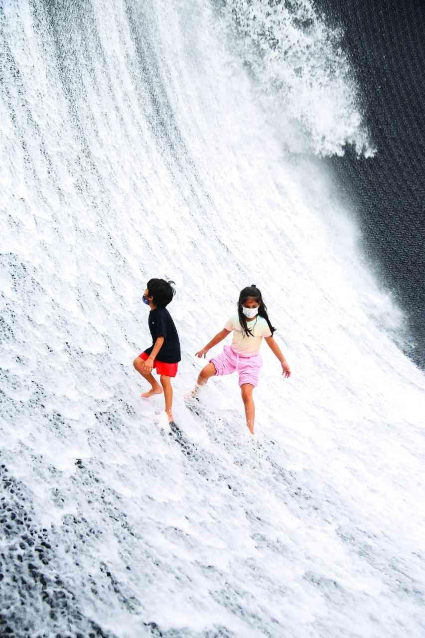 الصورة : » طفلان يستمتعان بشلالات إكسبو